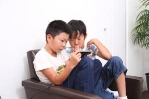 腰痛、肩こりを引き起こす悪い姿勢でゲームする子供たち